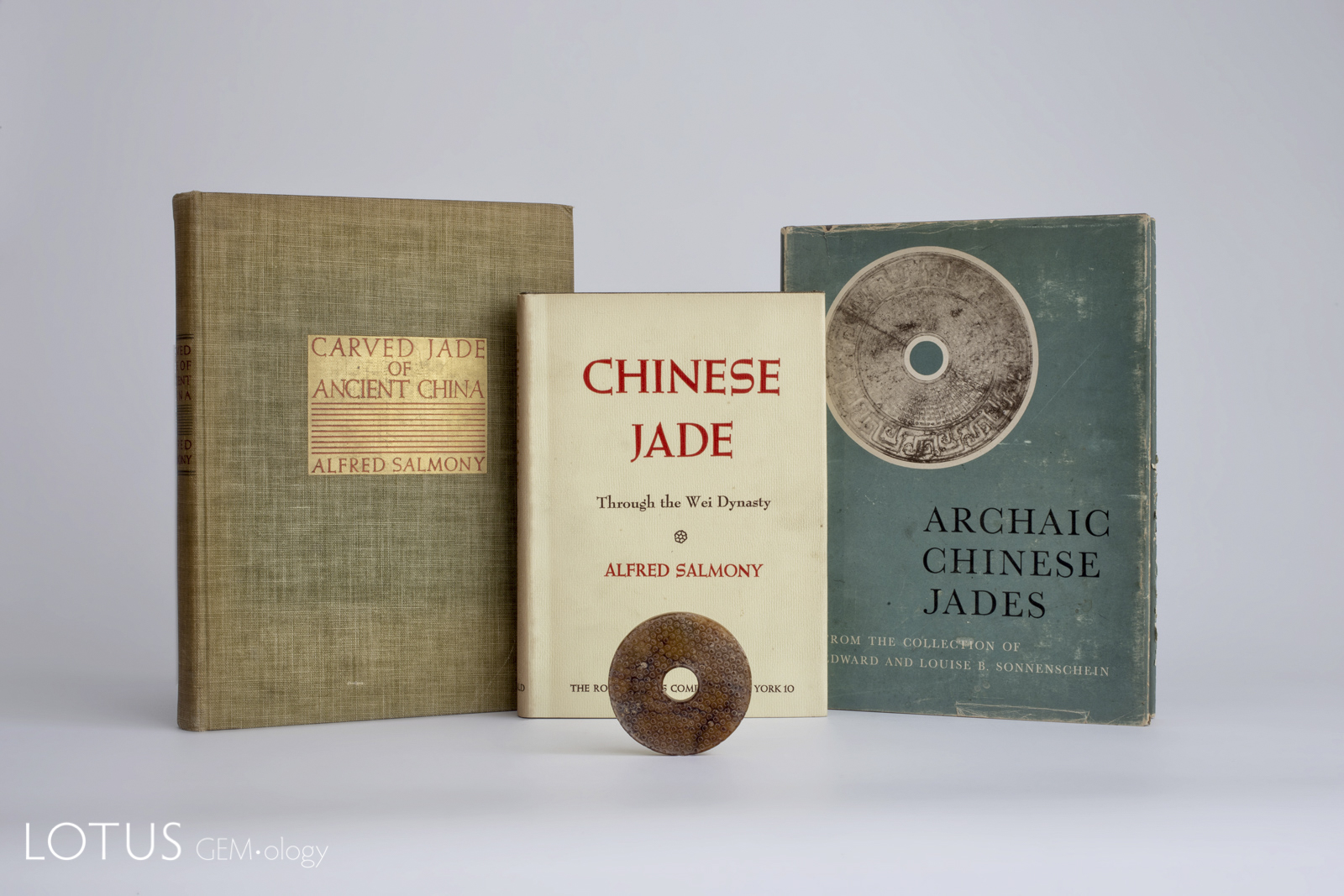Alfred Salmony's three important books on jade from 1938, 1963 (published posthumously) and 1952, along with a modern replica of an archaic Chinese jade bi.