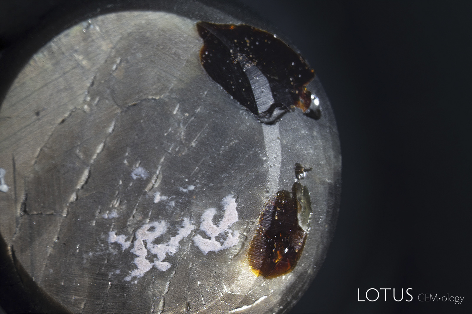 Left: Two large pits on the back of the star sapphire in question. One can see the brown dopping varnish (the white areas are adhesive from tape).