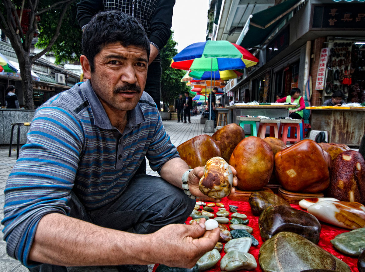 A Uighur man showing what looks like Chinese nephrite jade in Guangzhou's Hualin Street jade market. From Lotus Gemology.