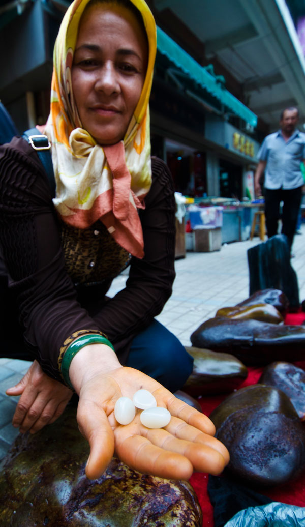 A Uighur woman showing what looks like Chinese nephrite in Guangzhou's Hualin Street jade market. From Lotus Gemology on jade and its imitations.
