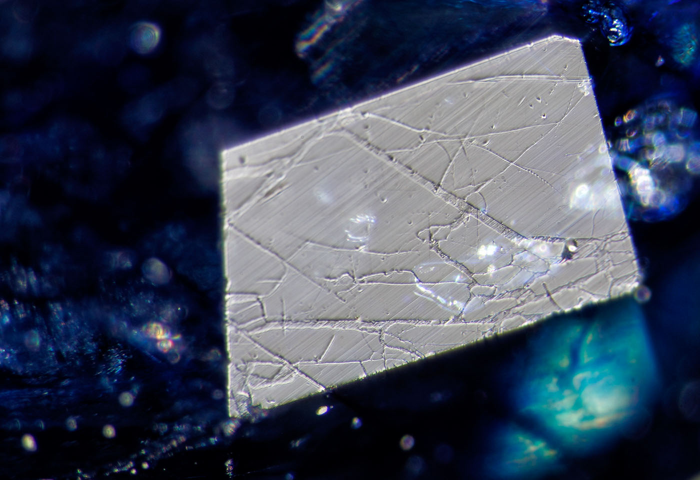 Figure 10. A small facet viewed in reflected light reveals a network of fissures filled with glass. The low hardness of the glass shows serious undercutting compared with the surrounding sapphire. Surface-incident fiber-optic illumination. (Photo: Wimon Manorotkul, Lotus Gemology).