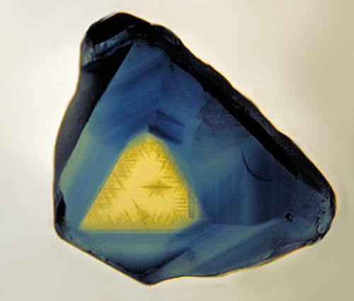 Figure 6.  Outer triangulation… A thin polished slice of an Australian sapphire, looking parallel to the c-axis (parallel to the prism faces. The three-fold symmetry is clearly visible. Photo © Richard W. Hughes
