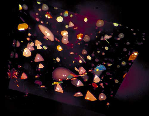 Figure 7. …equals inner triangulation Decrepitation halos surround minute primary negative crystals in the pinacoidal plane of a basaltic Thai/Cambodian ruby, creating a sea of highly characteristic thin-film fluid inclusions. One can clearly see the three-fold symmetry of these distinctive features. Photo © Richard W. Hughes