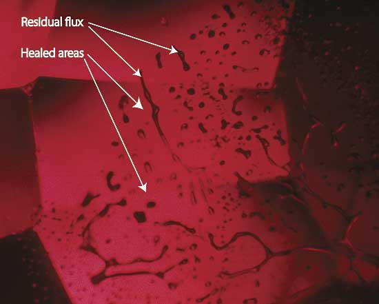 Moderate magnification reveals a flux-healed fracture in a Mong Hsu ruby from Burma. The irregular dark areas are pockets of residual flux, while the red areas in between are where the once open fracture has healed shut with microscopic amounts of what is essentially synthetic ruby. In some places, the flux residue appears transparent. This is an illusion produced by reflection off the surfaces of the flux pockets. Photo: R.W. Hughes. Lotus Gemology.