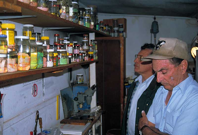Lenny Cram (far right) and Terry Coldham in Lenny Cram's shed outside his house in Lightning Ridge, Australia.