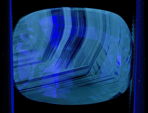 Figure 4. Another blue sapphire showing chalky fluorescence corresponding to the colorless portions of the gem. When seen, this strong chalky blue to green SW fluorescence is an extremely strong indication that the gem has been subjected to high-temperature heat treatment. Note that this fluorescence often appears in patterns that resemble the graining of wood. Photo: Richard W. Hughes; Nikon D200