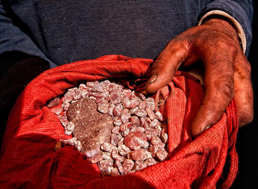 Figure 12. Handful of andesine near Zha Lin village, in Tibet's andesine mining district. Photo: Richard W. Hughes