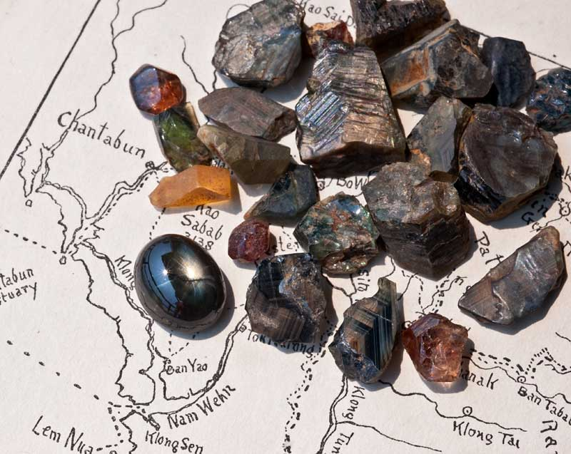Rough gems from Khao Ploi Waen, along with one 12-rayed black star sapphire cabochon.