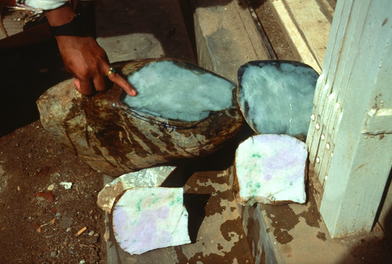 Sectioned jade boulder at Hpakan. The thick brown skin typically hides all traces of color inside. Only cutting reveals the true value. The pictured stone contains jade of both green and lavender colors