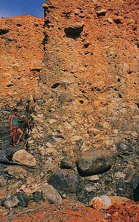Figure 4. At the Ka Htan West mine, located between Lonkin and Tawmaw, large peridotite boulders can be seen at the base of this 15-m-high wall of Uru Boulder Conglomerate. Photo © George Bosshart.