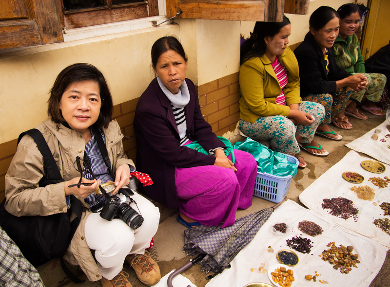 Figure 5. Wimon Manorotkul (left) joins dealers displaying rough gems in Mogok's market. Over fifty different types of gems are found in the Stone Tract. Photo: E. Billie Hughes