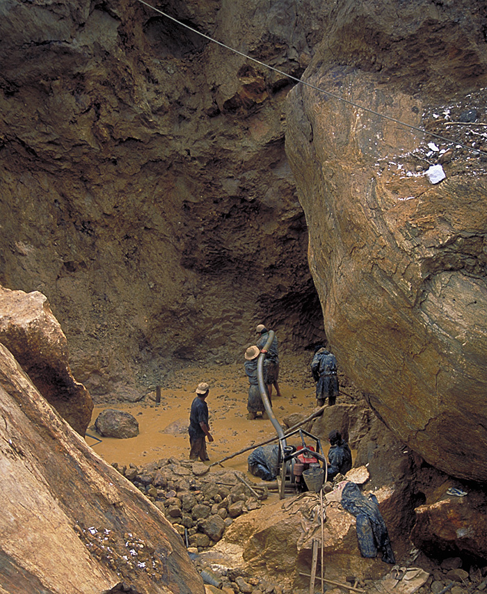Miners at Inn Chauk, just north of Mogok, are dwarfed by massive limestone boulders as they hunt for pigeon's blood rubies.