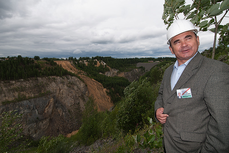 Top: The small village of Malysheva, perches on the very edge of the large open trench (just beyond the trees in the background). Photo: Warren Boyd  Bottom: Evgeny Nikolayevich Kazeyev, then of Zelen Kamen (ZK), standing above the large open trench at Malysheva. This pit was created and mined from 1956–1971. Photo: Richard W. Hughes