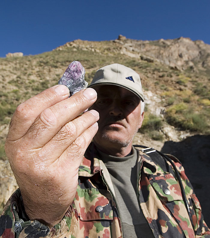 A miner at Kuh-i-Lal holds up a piece of impure spinel. Photo: Richard W. Hughes