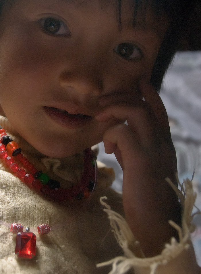 Why travel? Let us answer that riddle with a picture. The gem is a piece of ordinary red glass, worth perhaps a dollar. But gaze into this Kyrgyz' girl's eyes and you will find discover priceless treasure. Gems are accessories. Life and living is about people. Photo: Richard W. Hughes
