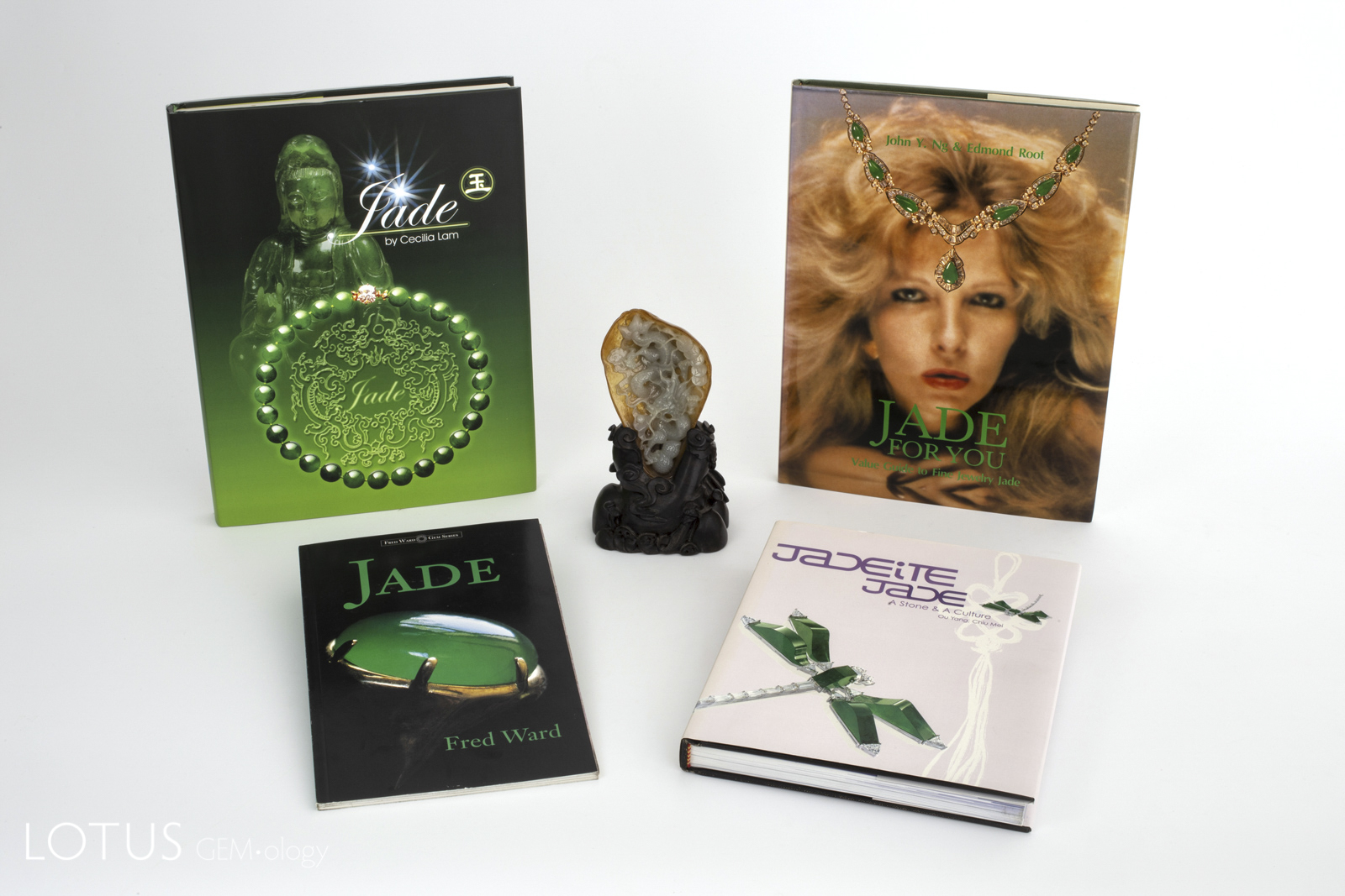 Four classic modern books on jade surround a Chinese carving in Burmese jade. Clockwise from top left: Jade by Cecilia Lam; Jade for You by John Ng & Edmond Root; Jade by Fred Ward, and Jadeite Jade: A Stone & a Culture by Ou Yang Chiu Mei.