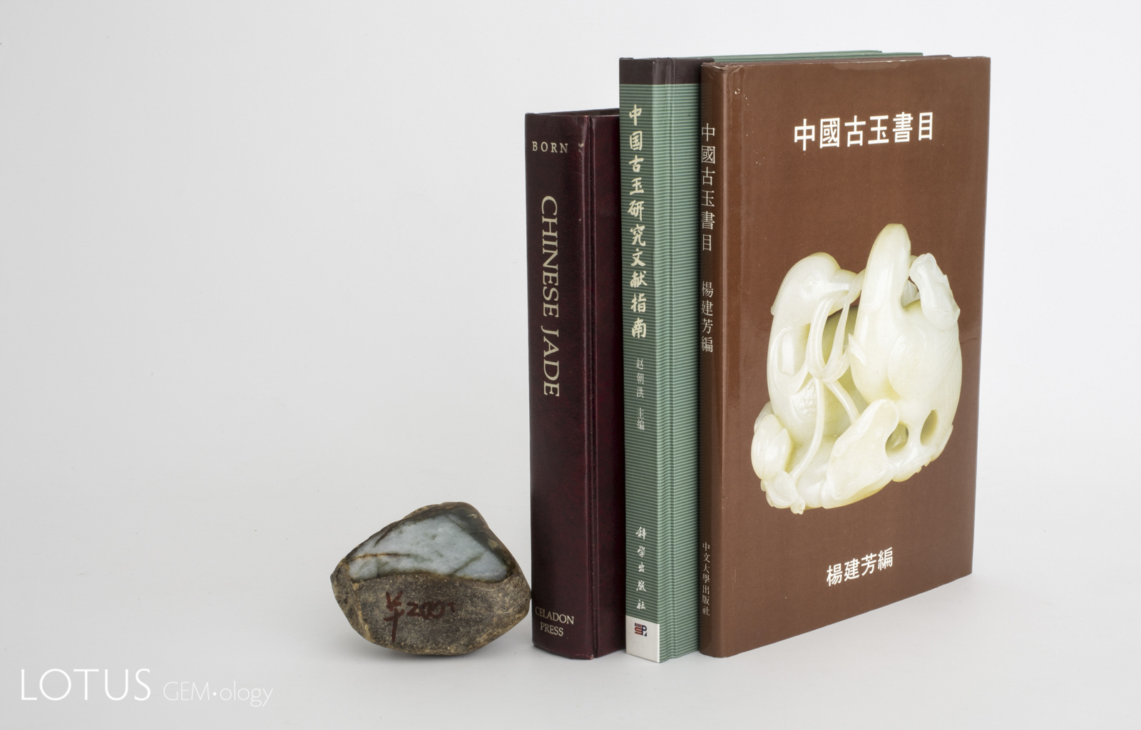 For the collector, bibliographies are essential references. From left to right: Born, Zhou and Yang. At left is a sliced piece of rough Burmese jadeite.