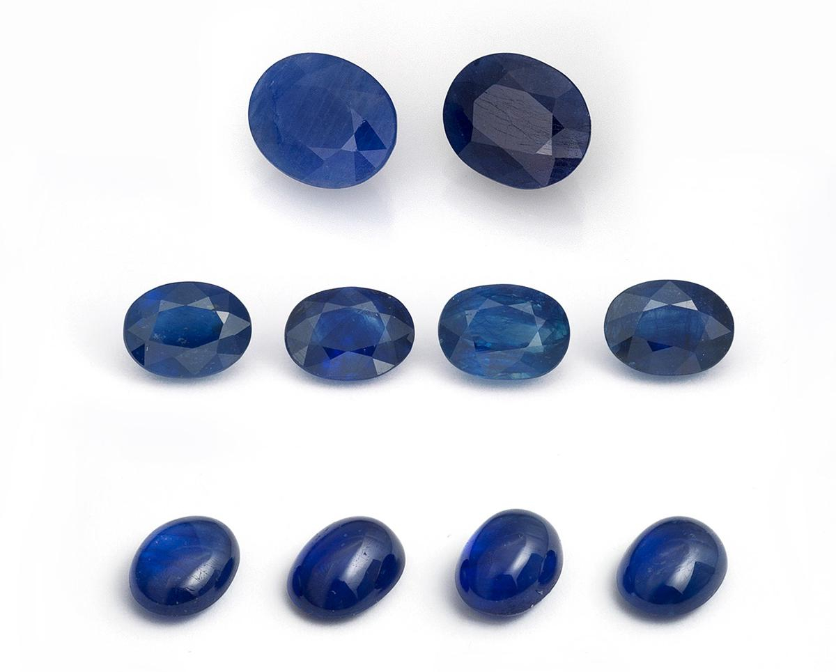Figure 2. Two first-generation cobalt-doped glass-filled sapphires (top row; 3.49 & 3.37 ct), along with eight latest-generation cobalt-doped glass-filled sapphires ranging from 1.50–2.25 ct each that were tested as part of this study. Note the far lower clarity of the first-generation stones. (Photo: Lotus Gemology's Wimon Manorotkul).