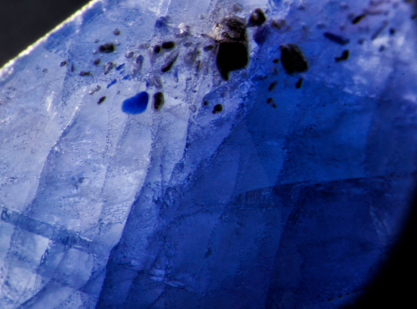 Figure 5. Left: Blue pool of cobalt-doped glass fills a surface cavity in this first-generation Tanusorn stone. Dark-field illumination. Right: The same inclusion in reflected light reveals the lower luster of the glass filler. Oblique fiber-optic illumination. (Photos: Richard Hughes). Lotus Gemology.