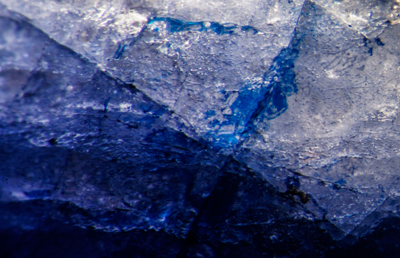 Figure 6. Blue cobalt-doped glass fills a surface-reaching fissure in this first-generation stone. Oblique fiber-optic illumination. (Photo: Wimon Manorotkul, Lotus Gemology).
