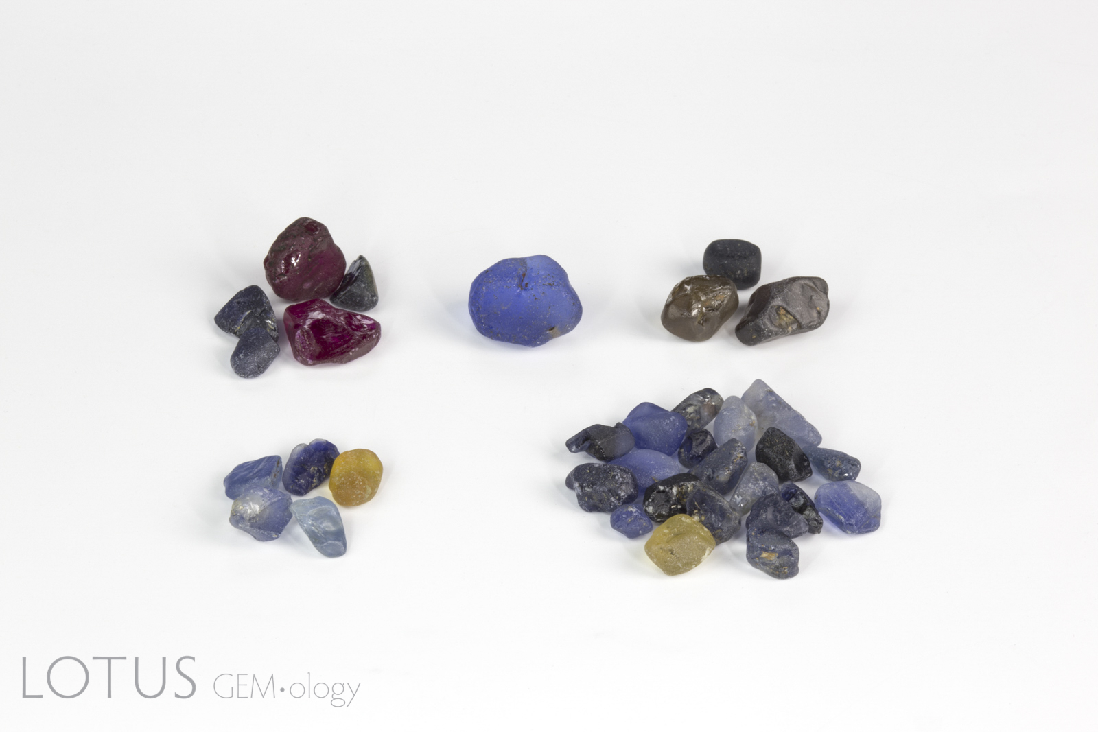 Rough gem samples purchased at Colorline's Ilakaka office (clockwise from top left): Verneuil synthetic corundum, blue glass, zircon and spinel, coated natural sapphire; natural untreated blue and yellow sapphire. Note that these were purchased just to get a snapshot of what was in the market, even though we knew many were not what they were represented as. Photo: Wimon Manorotkul.