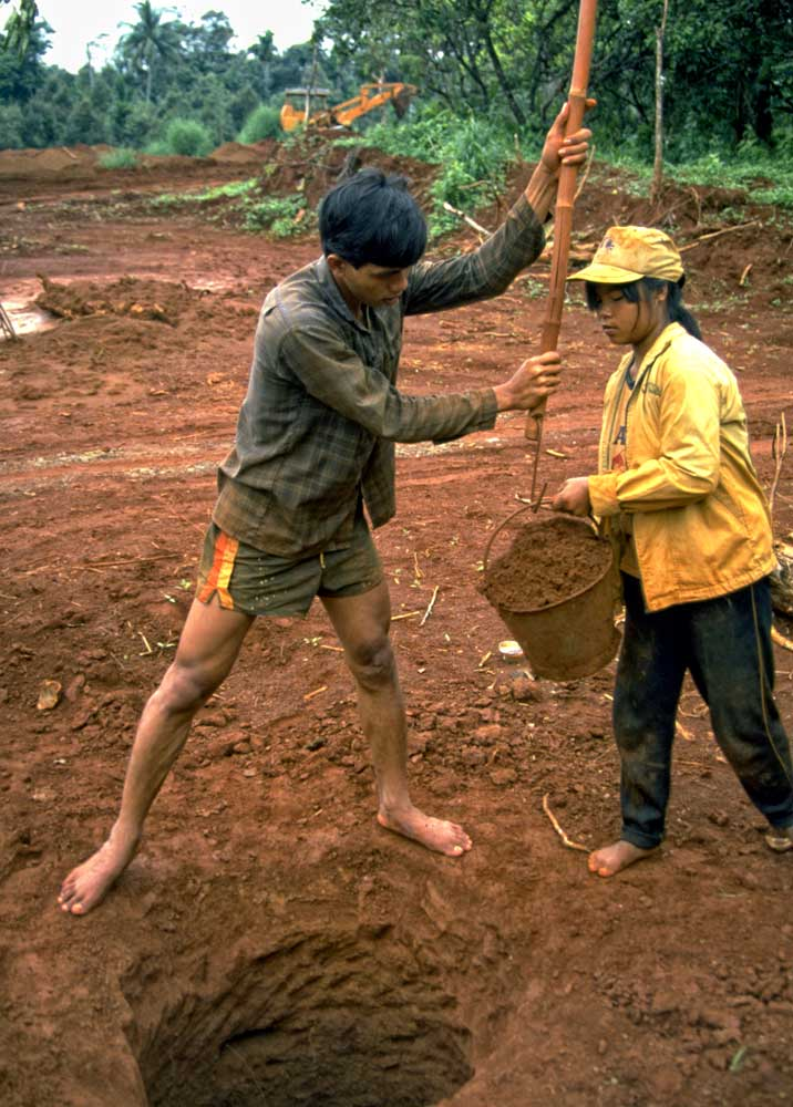 Pit miners at Khao Ploi Waen, ca. 1980. While the mine was real, the cut stones being sold just off camera were anything but, consisting of doublets made of thin slices of natural green sapphire on top of Verneuil synthetic corundum. Photo: Richard W. Hughes
