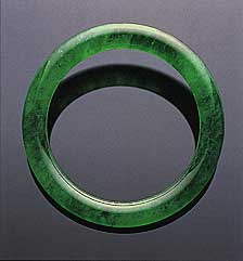 Figure 6. Believed to date back at least four millennia in China, the jade bangle is both one of the oldest and one of the most important pieces of jewelry in the Chinese culture. This superb jadeite bangle sold for US$2,576,600 at the Christie's Hong Kong November 1999 auction. The interior diameter is 49.50 mm; the jadeite is 8.36 mm thick. Photo courtesy of and © Christie's Hong Kong and Tino Hammid.