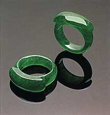 "Figure 8. Note the small patches of a slightly paler color on the shank of one of these ""emerald"" green saddle rings (21.27 and 21.65 mm, respectively, in longest dimension). Photo courtesy of and © Christie's Hong Kong and Tino Hammid."