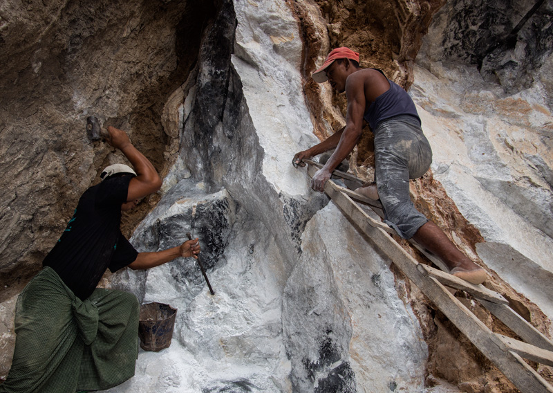 Figure 3. Ruby miners preparing to set an explosive charge in the marble at Sagyin, just north of Mandalay. Note the clay band cutting through the marble. Hydrothermal fluids from this clay are thought to have supplied the aluminum and chromium necessary for the growth of ruby and spinel in marble. Photo: E. Billie Hughes