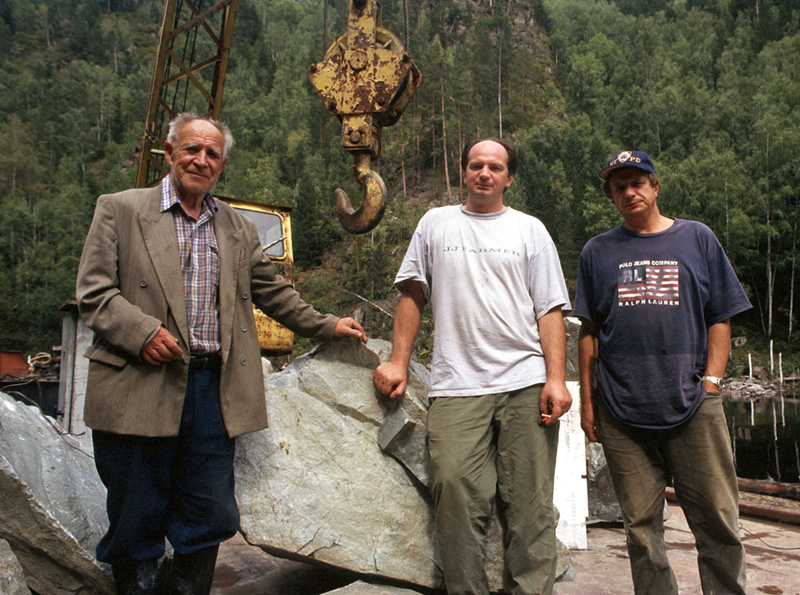 "Mikhail ""Misha"" Khrolenko (center) and his father Yakov Borisovich(left) and brother Sergei (right), owners of the Khakassia jade mines. They are standing in front of a huge chunk of Khakassia jadeite. Photo: © Richard W. Hughes"