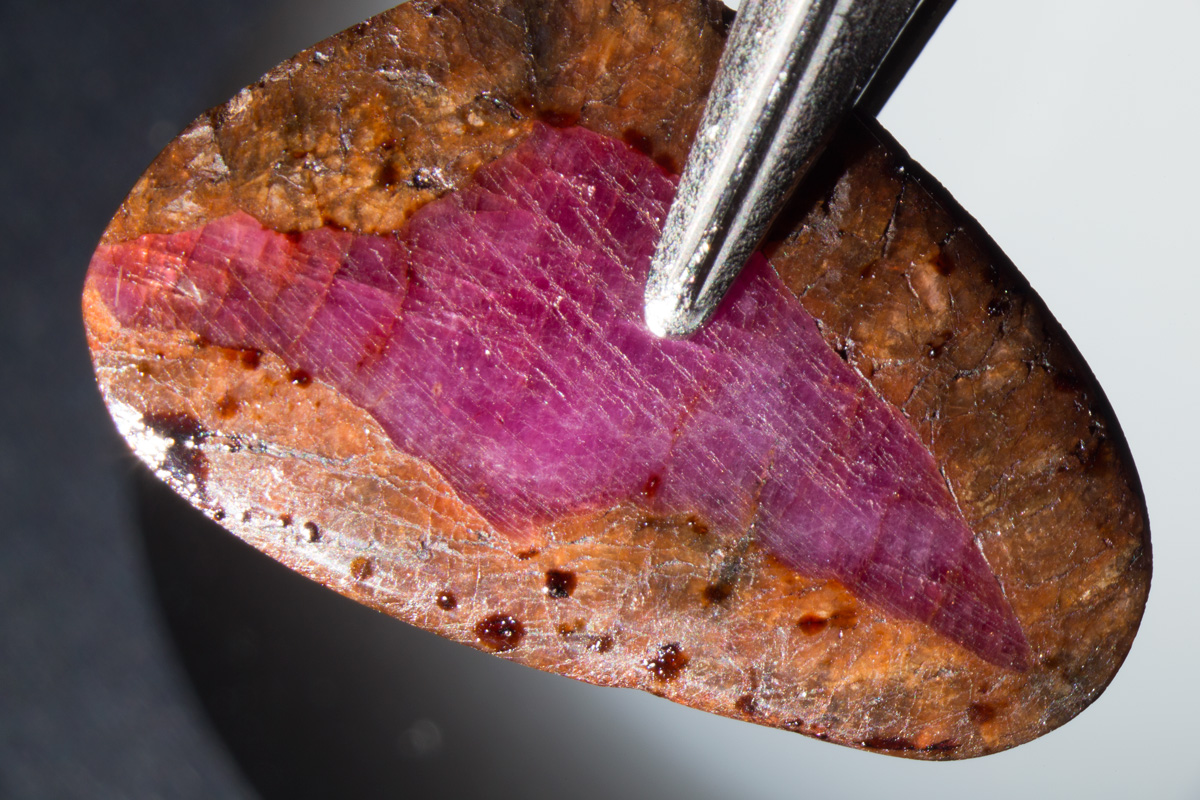 This unusual overgrowth of spinel on ruby was placed by its owner into an oven and gently heated, causing a brown filler to ooze out of the fissures.